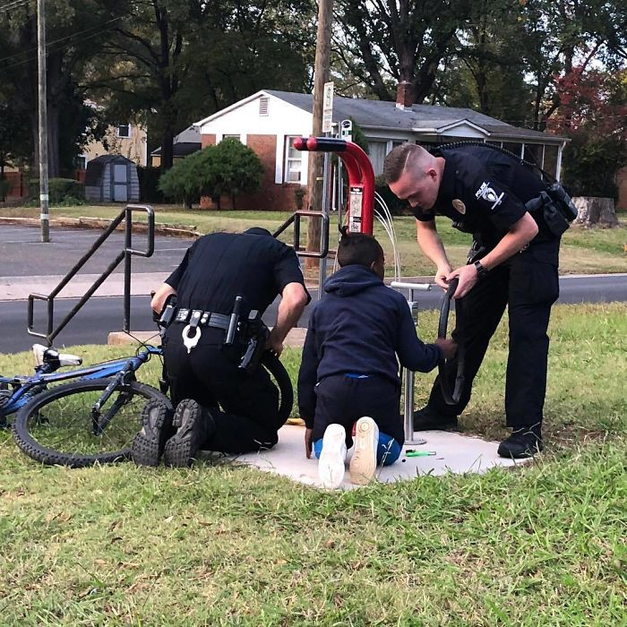 Two Officers Stopped To Help A Young Boy Change A Bike Tire After They Noticed He Was Struggling On His Own