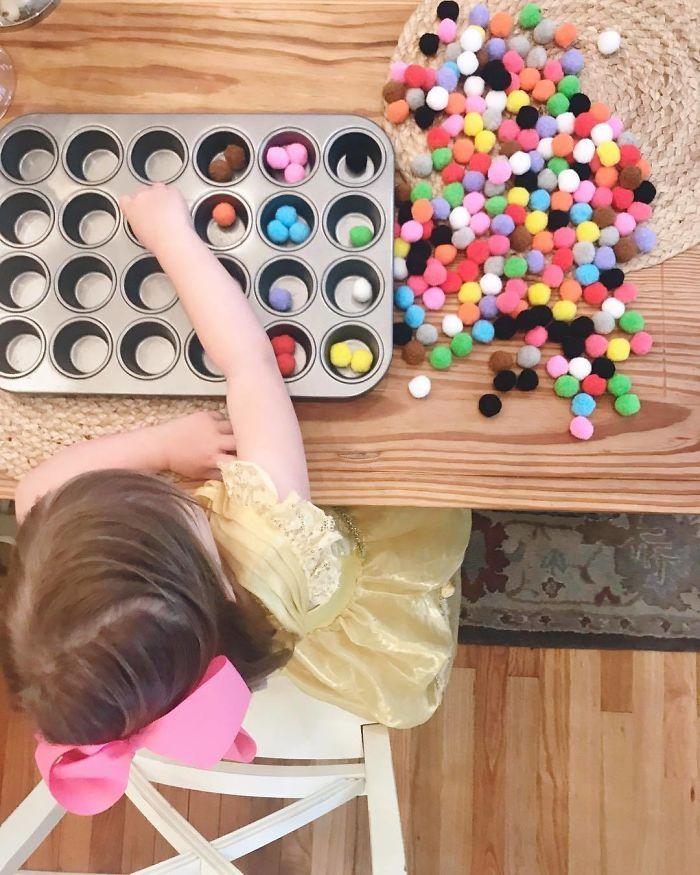 Pídele a tu hijo que separe cosas pequeñas como bolitas de fieltro o pasta de colores en un molde para magdalenas
