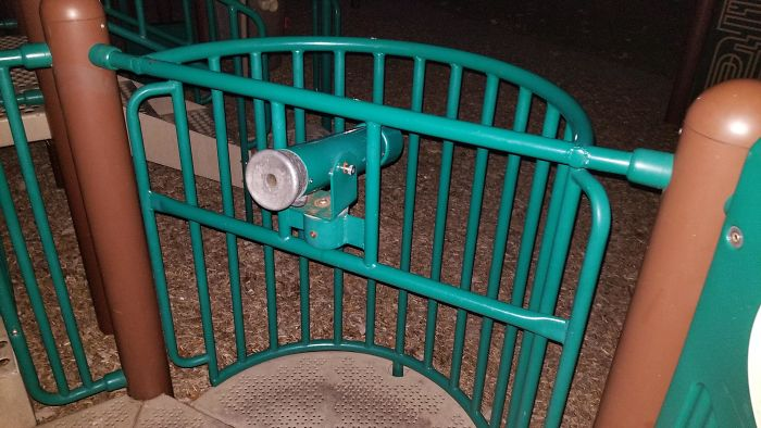 Playground Telescope Aimed At Ground And In Front Of Metal Bars