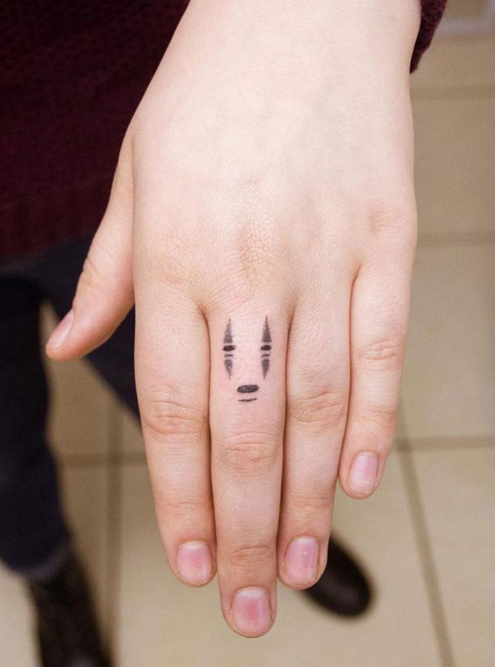 Tiny No Face Finger Tattoo