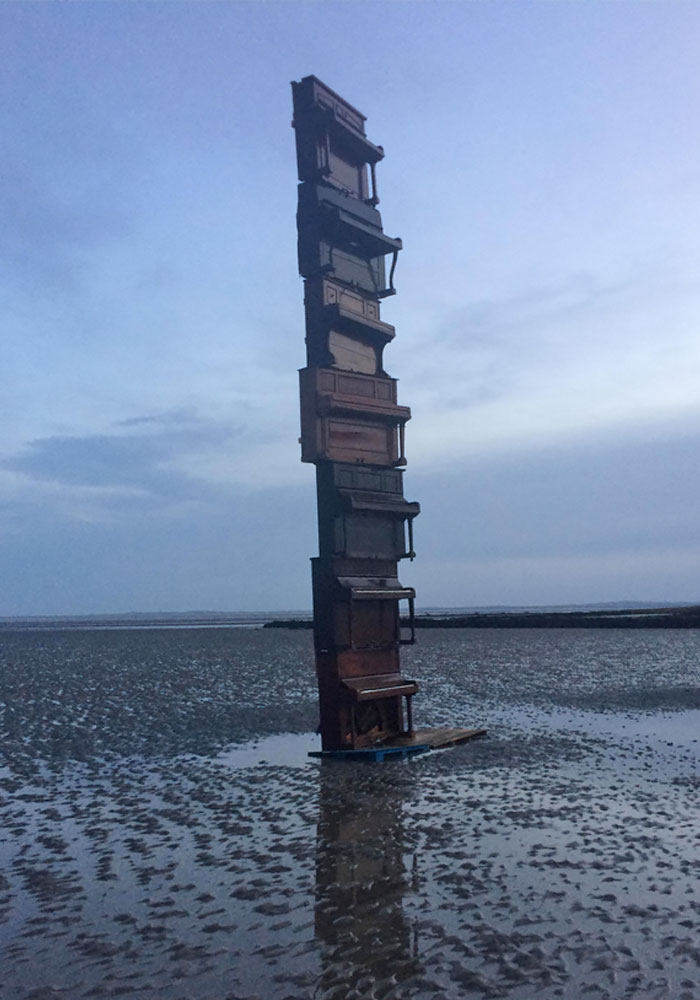 This Stack Of Pianos On A Beach At Low Tide