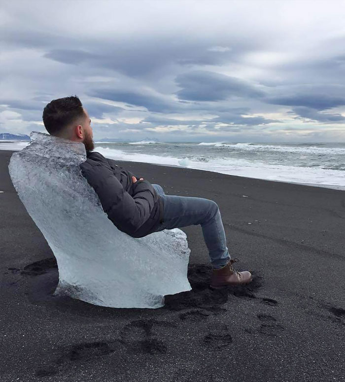 A Sea Weathered Chunk Of Glacial Ice Made A Perfect Chair On A Black Sand Beach In Iceland