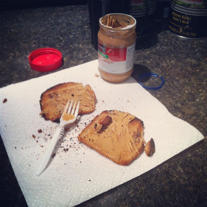Burnt Loaf Heels With Generic Brand Peanut Butter, Spread With A Plastic Fork. Prepared In The Kitchen, Eaten, While Frowning, At The Desk