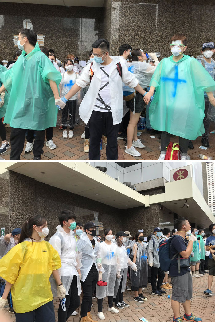 Volunteers In Ponchos Marked With A Blue Cross, Wearing Surgical Masks And Goggles, Form A Human Wall To Protect The First Aid Area Right Outside Admiralty Station, Across The Street From The Hong Kong Central Government Offices