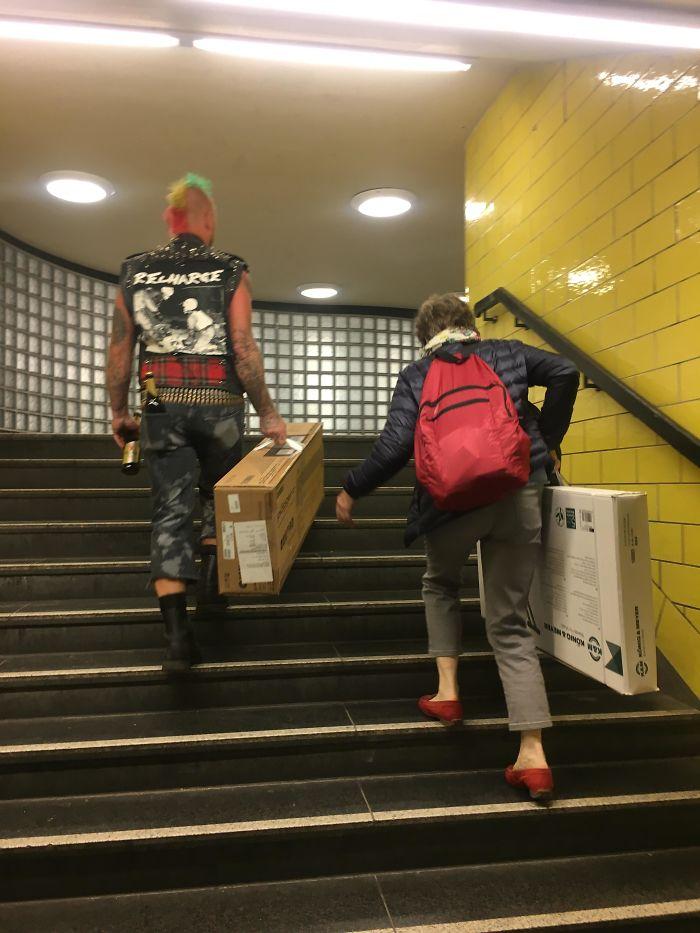 Un punki ayudando a una mujer con su pesada carga en el metro de Berlín