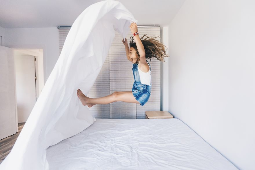 Little Girl Jumping On The Bed And Having Fun