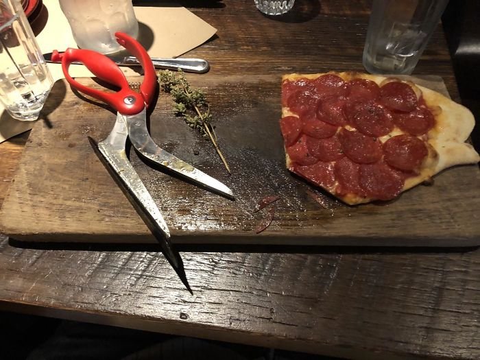 Pizza With Scissors On A Slab Of Wood With Historic Grease Soaked In.