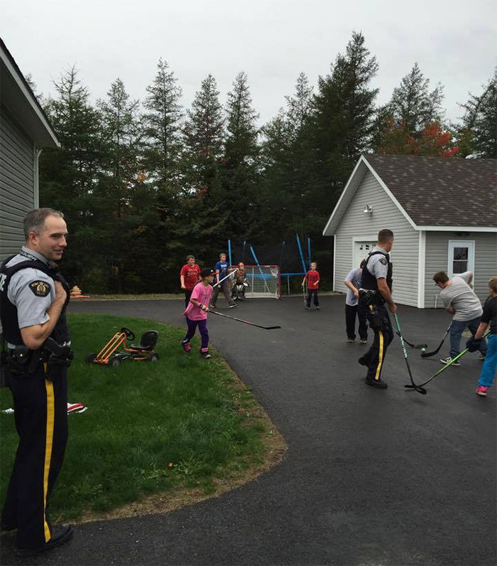 Police Playing Ball Hockey With The Neighborhood Kids. Just A Normal Day In Canada