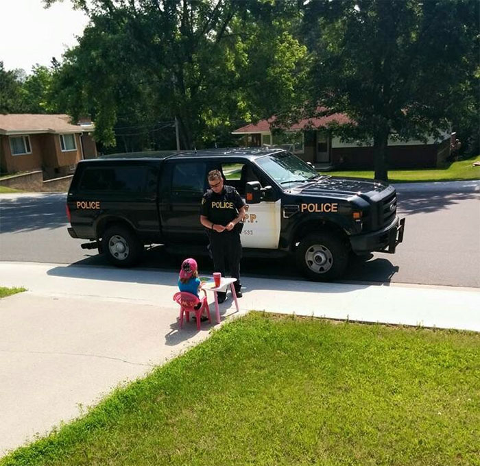 Police Officer Stops To Buy A Drink From A Little Girl At A Lemonade Stand In Kenora, ON, Canada