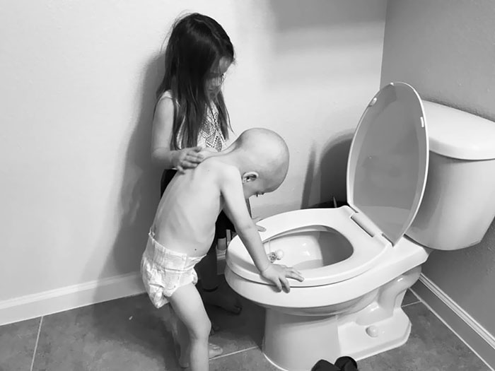 5-Year-Old Girl Gently Supporting Her 4-Year-Old Brother As The Side Effects Of Chemotherapy Disrupt Their Playtime