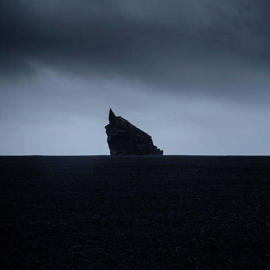 Volcanic Rock Towering Over An Endless Black Desert