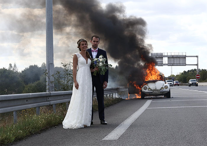 Just Married Couple In Front Of Their Burning Car