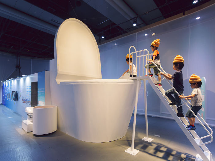 Japanese Children Wearing Feces-Shaped Hats Slide Into A Giant Toilet