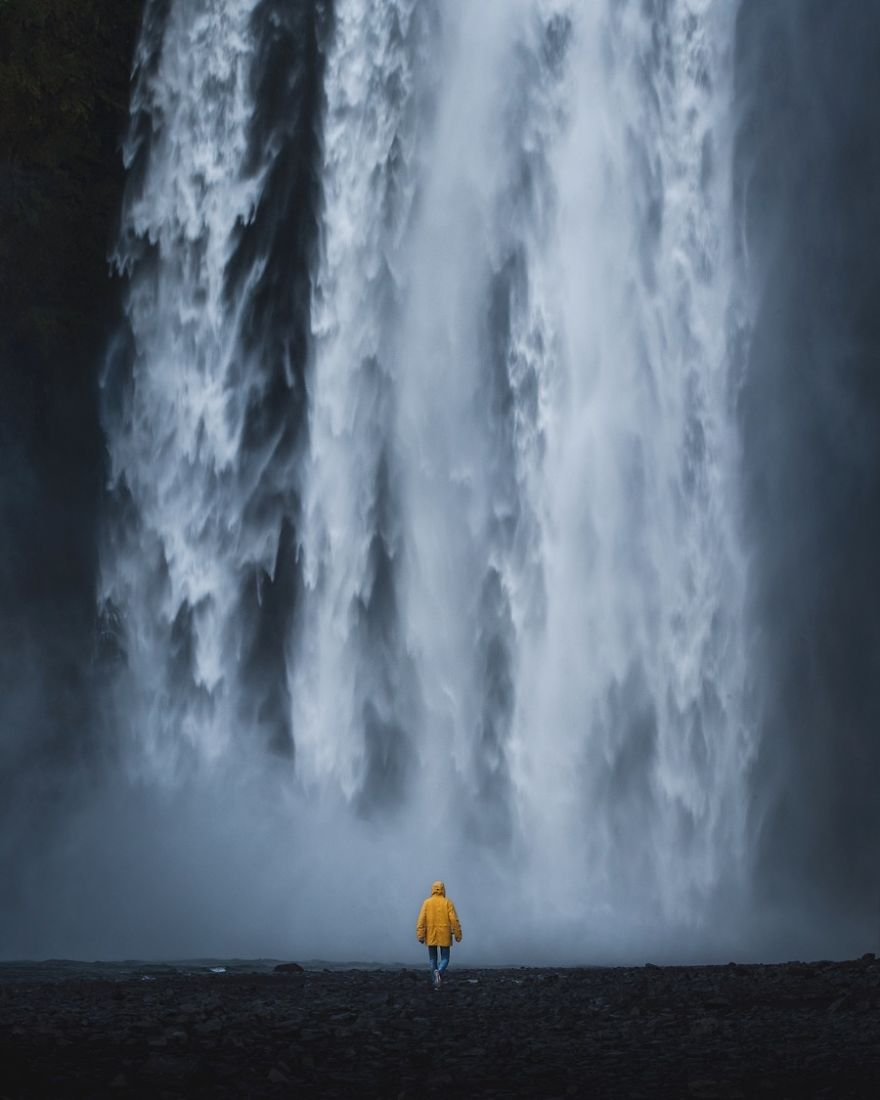 A Person In Yellow At Skogafoss