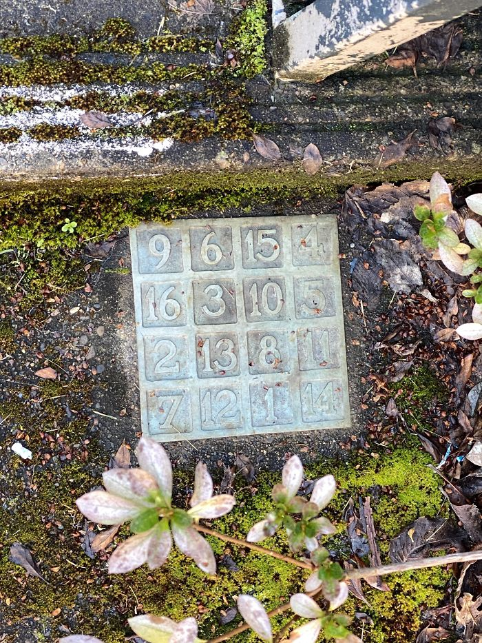 Plaque With Numbers Inscribed On It. Found On The Sidewalk Outside A Building At My University