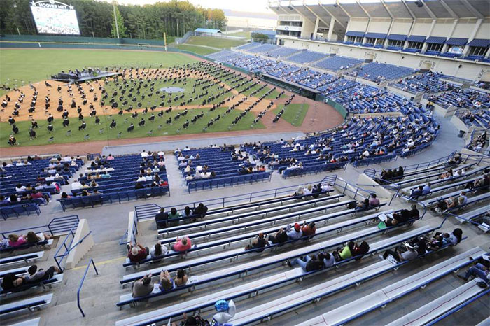 Seniors Sit On A Baseball Field During A Socially Distanced Graduation Ceremony