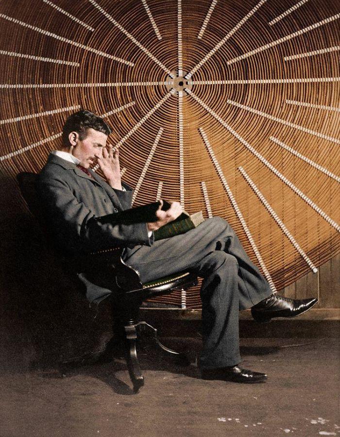 Nikola Tesla, leyendo 'Theoria Philosophiae Naturalis', frente a la bobina espiral de su transformador de alta frecuencia, en Nueva York