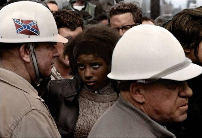 Aprox. 1960: Manifestación por los derechos civiles. Mujer negra mirando a un hombre con la bandera confederada en su casco