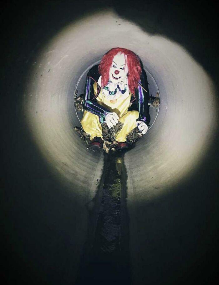 Maniquí payaso atado a una reja en una tubería de desagüe, a 0,8 kms de la entrada