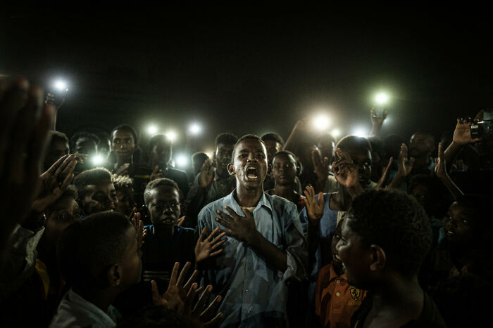 A Young Man, Illuminated By Mobile Phones, Recites A Poem While Protestors Chant Slogans Calling For Civilian Rule, During A Blackout In Khartoum, Sudan