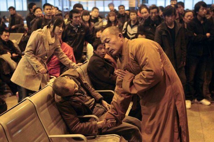 A Monk Prays For An Elderly Man Who Had Died Suddenly While Waiting For A Train In China.