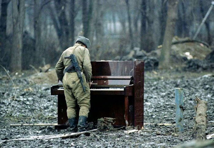 Russian Soldier Playing An Abandoned Piano In Chechnya