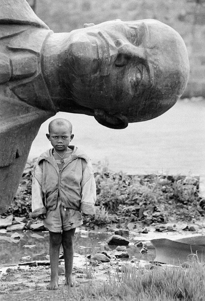 Boy Standing In Front Of Fallen Statue Of Lenin, Ethiopia, 1991