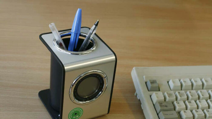 Camera Hidden In Pen Holder, With The Lens Seen In The Centre Of The Green Sticker
