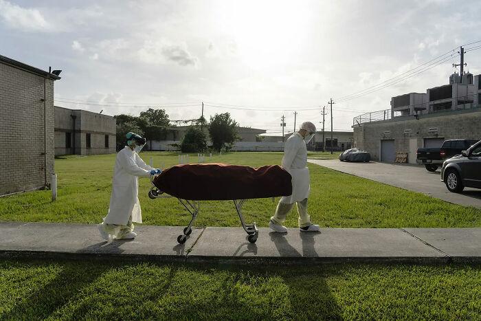 Personal médico con equipo de protección sacando una camilla con el cadáver de un paciente fallecido por Coronavirus, para llevarlo a un vehículo. 30 de Junio