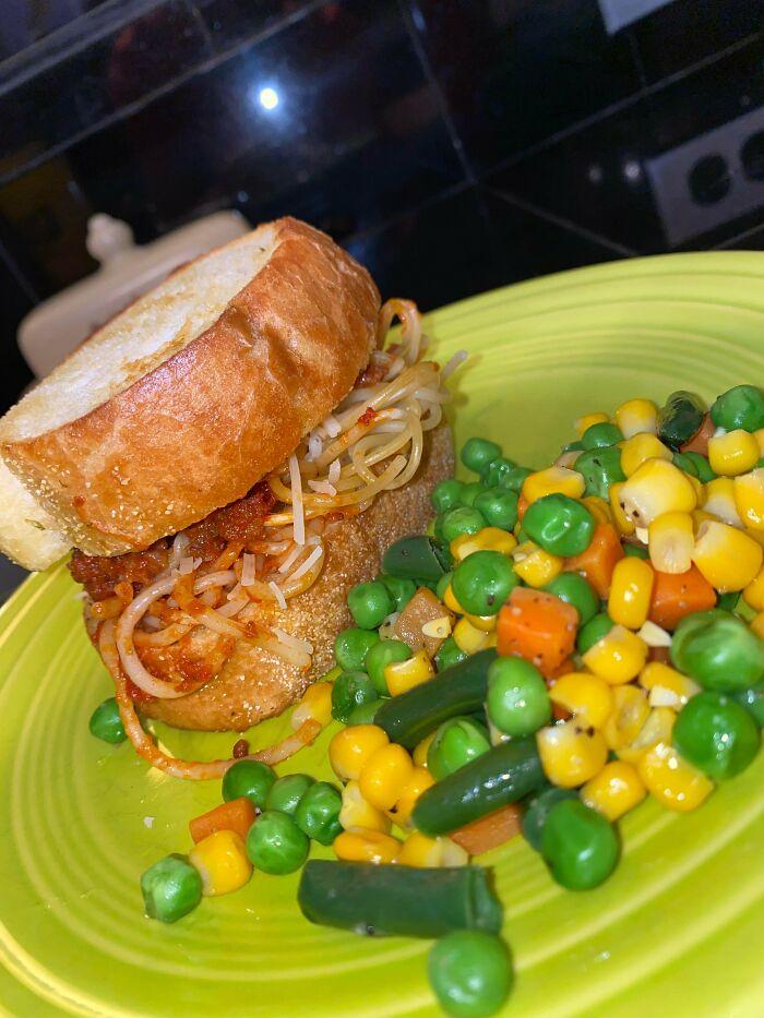 La cena de hoy es espaguetis entre pan de ajo con mezcla de verduras