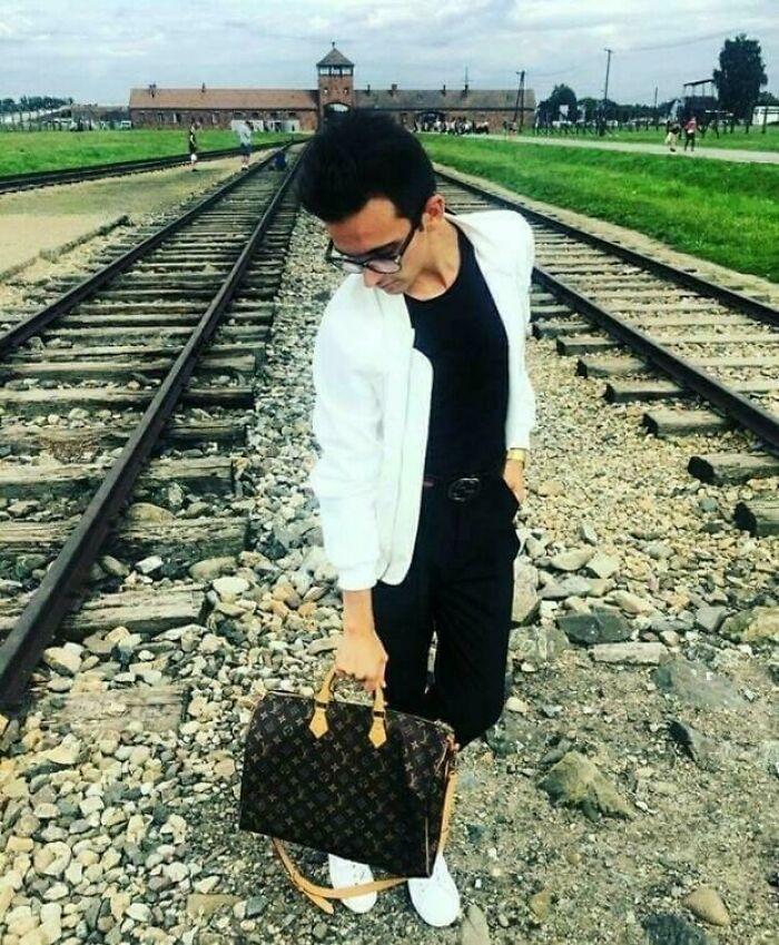 Dude Is Flexing His Louis Vuitton Bag On Auschwitz Train Tracks