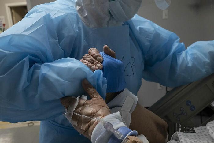 31 de Octubre. Trabajador médico dando la mano a un paciente de Covid mientras recoloca su cama