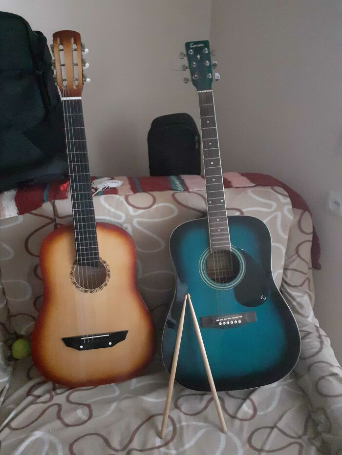 A Classic And An Acoustic Guitar And Practice Drum Sticks