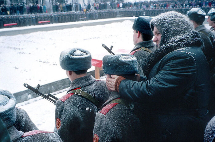 A Babushka Keeps The Ears Of Her Grandson Warm As He Takes An Oath Of Enlistment For The Russian Army. Volgograd, 1994. Photo Taken By Nikolai Ignatiev