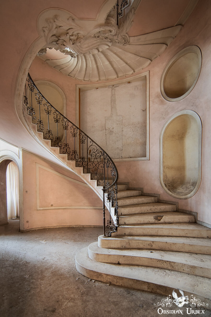 A Shell-Like Decoration Fans Out From The Top Of The Staircase Inside This Derelict House