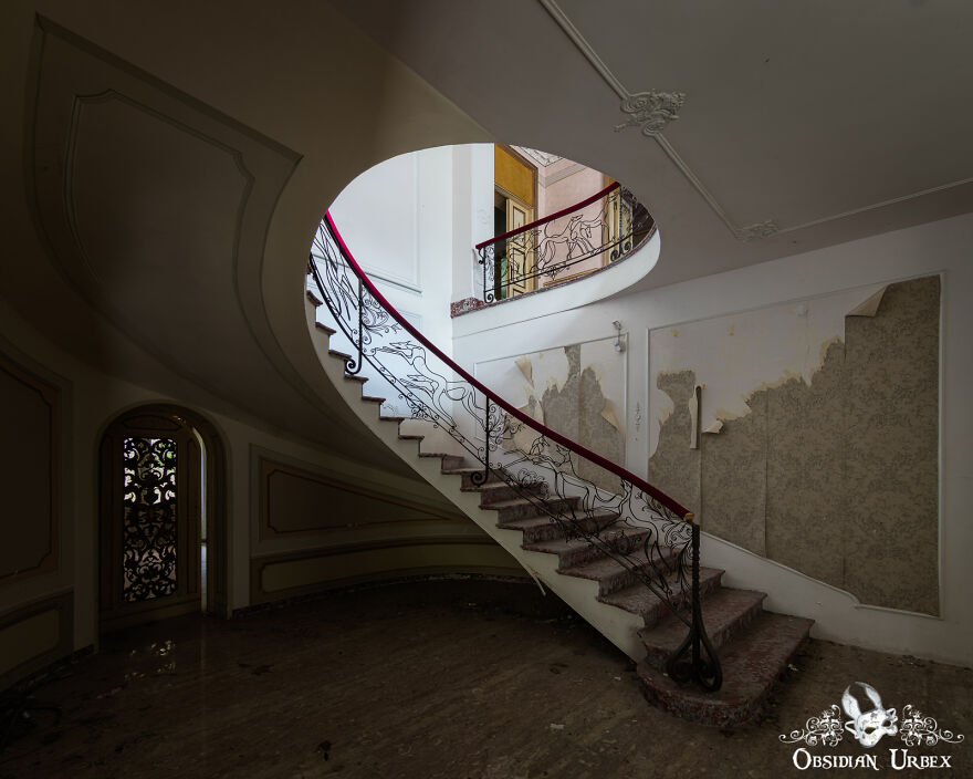 The Spiral Staircase Inside This Abandoned House Is Quite Unusual. It Has A Red Velvet-Covered Handrail, The Metal Work Depicts Dogs Running