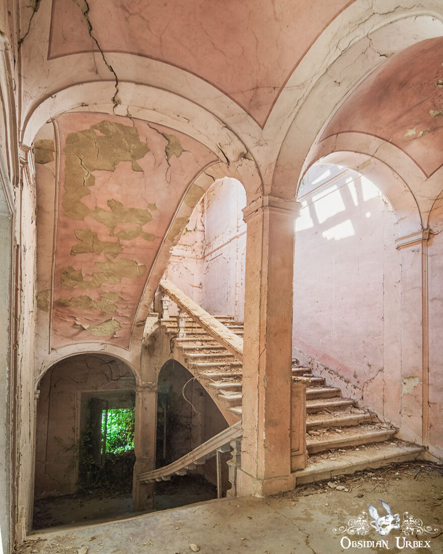 Delicate Pink Paint Peels From The Ceiling Above This Abandoned Staircase