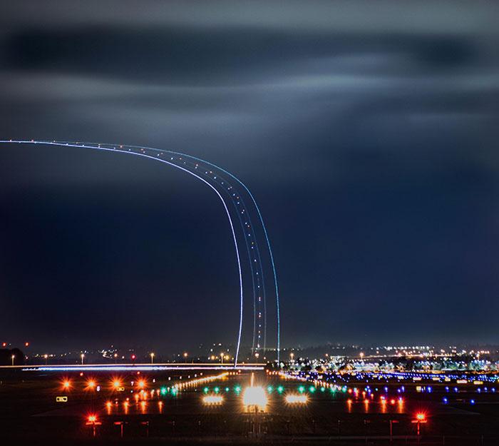 Autopista hacia el cielo. Exposición larga de 30 segundos de un avión que sale de la pista de aterrizaje