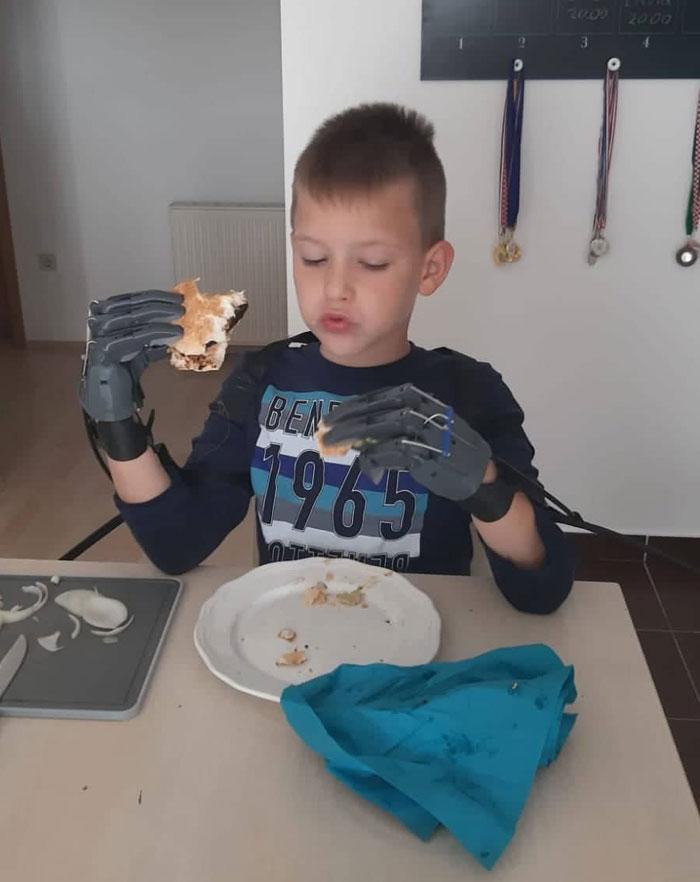 Mi amigo comiéndose una hamburguesa con las manos prostéticas que le he diseñado y construido