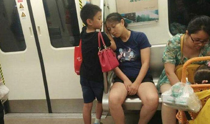 This Little Boy Gave Up His Seat To A Lady Who Entered The Train With A Stroller & Baby. Then As He Is Standing, His Mom Falls Asleep With Her Head On The Bare Railing