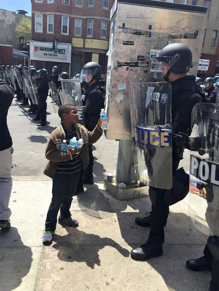This Boy Offering A Bottle Of Water To A Policeman During A Hot Day In Baltimore