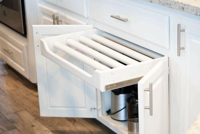 Este cajón tipo estante está montado en un gabinete de cocina. Esto es lo más lejos que se extrae y las barras no giran o salen