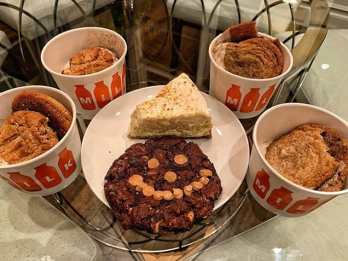 An Assortment Of Cookies And A Slice Chessecake To