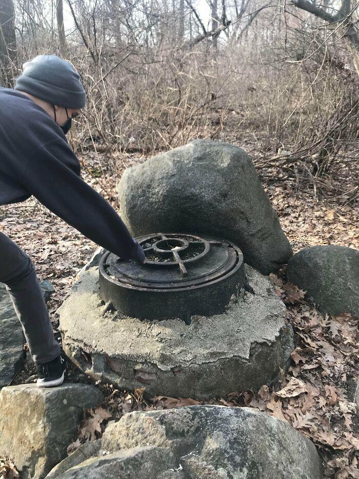 Esta estructura que encontré mientras caminaba en el bosque, la embocadura de metal es de aproximadamente 60 cm de ancho y parece que podría incómodamente encajar una persona en ella. Mis conjeturas son un pozo, una alcantarilla o una cápsula del tiempo. Para contextualizar, vivo en el este de Massachusetts. Planeamos regresar para abrirlo