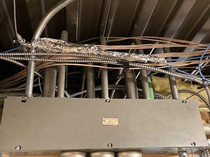 La empresa instaladora anterior pasó el Cat5 por la caja de conexiones principal y decidió proteger el cable con papel de aluminio
