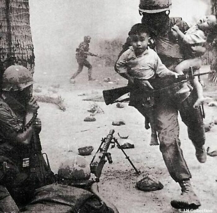 A U.S. Marine Rescues Two Vietnamese Children During A Gun Battle At The City Of Hue, During The Tet Offensive Of The Vietnam War - 1968
