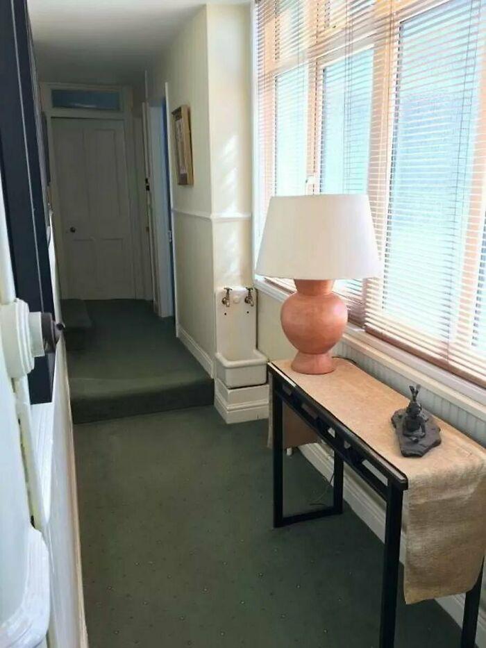 Un fregadero de forma inusual, posiblemente en un pasillo, visto en un listado de propiedades en una casa antigua. Parece bastante estrecho, probablemente demasiado pequeño para limpiar las botas