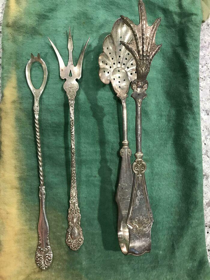 Cuchara abierta con pinchos; tenedor tipo tridente; pinzas con pata de pollo y cuchara perforada. Todo de plata antigua