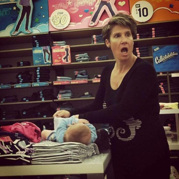 """""""Taking A Picture Of Me???"""" - Woman Changing Her Baby's Dirty Diaper On Top Of An Old Navy Clothing Display"""