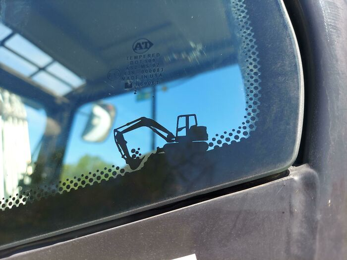 There's A Cute Little Excavator Graphic On The Window Of This Excavator